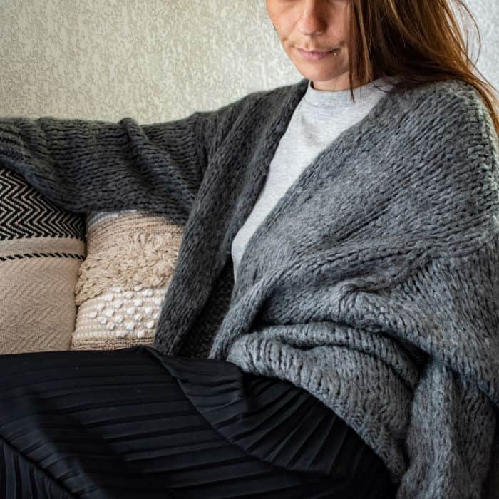 femme assie portant un gilet en laine long gris foncé