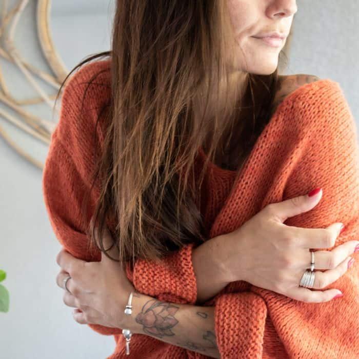 femme portant un pull oversize orange pendant l'hiver