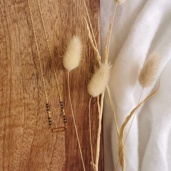 collier doré fin pendentif oval petites perles noires