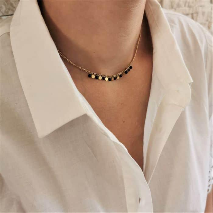 femme portant un collier ras de cou doré et noir