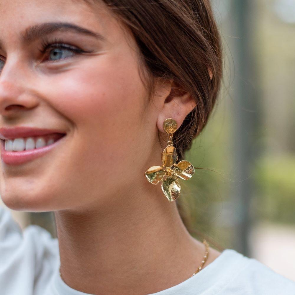 femme portant boucle d'oreilles fleur dorée pendante