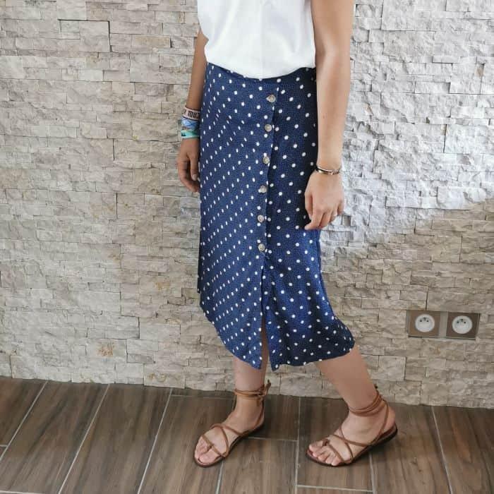 femme portant une jupe mi longueur bleu à pois blancs