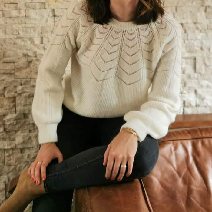 femme portant un pull blanc détail ajouré sur le col