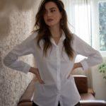 femme portant une chemise blanche longue en coton épais bien coupée