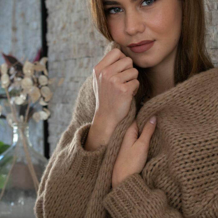 femme se lovant dans une maille douce beige