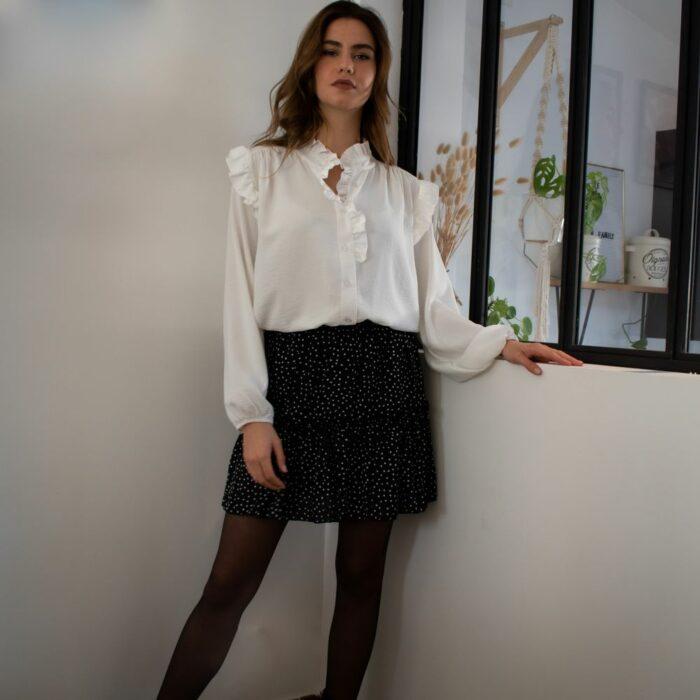 femme portant un look composé d'une chemise blanche et d'une jupe courte à volant noire