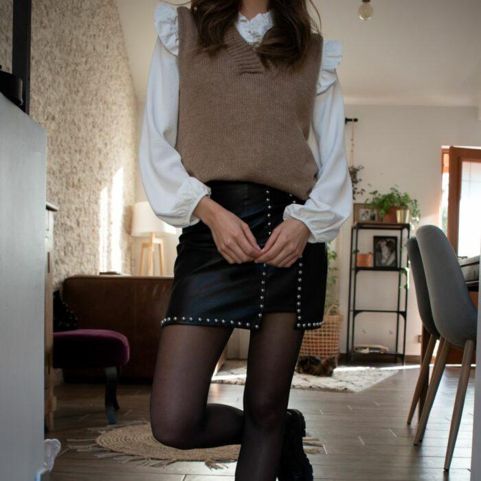 femme portant une jupe en cuir noire cloutée et un pull sans manche beige