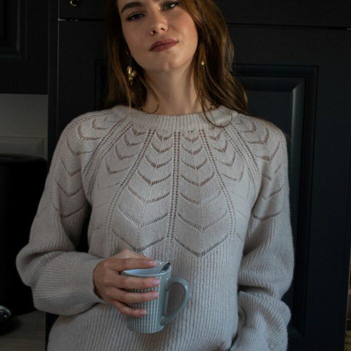 femme tenant une tasse de café dans la cuisine et portant un pull maille d'hiver écru avec détails ajourés