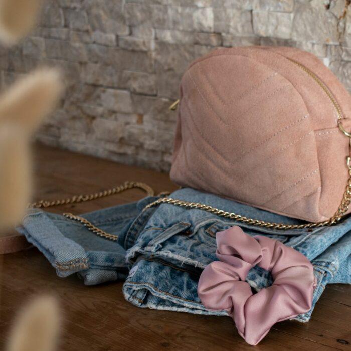 sac en cuir rose poudré posé sur un meuble