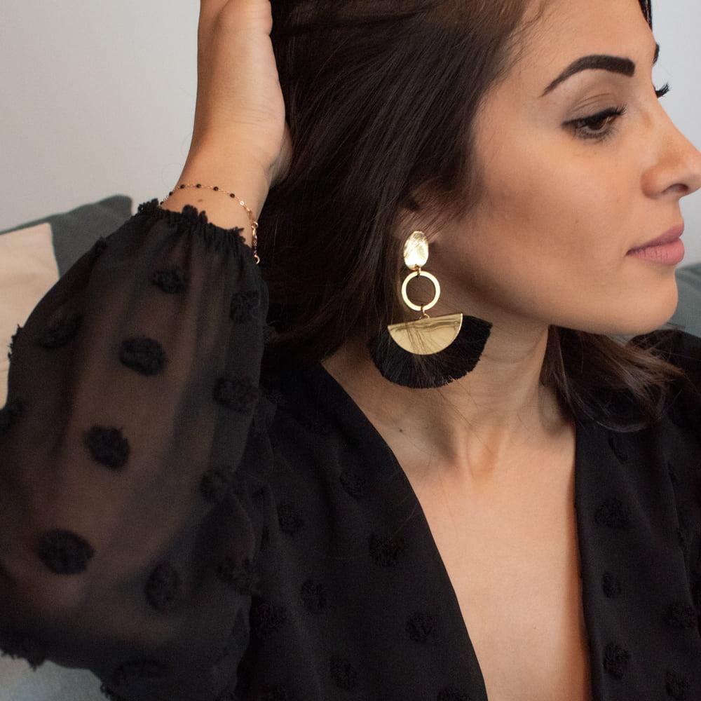 femme portant une paire de boucles d'oreilles dorées à franges noires