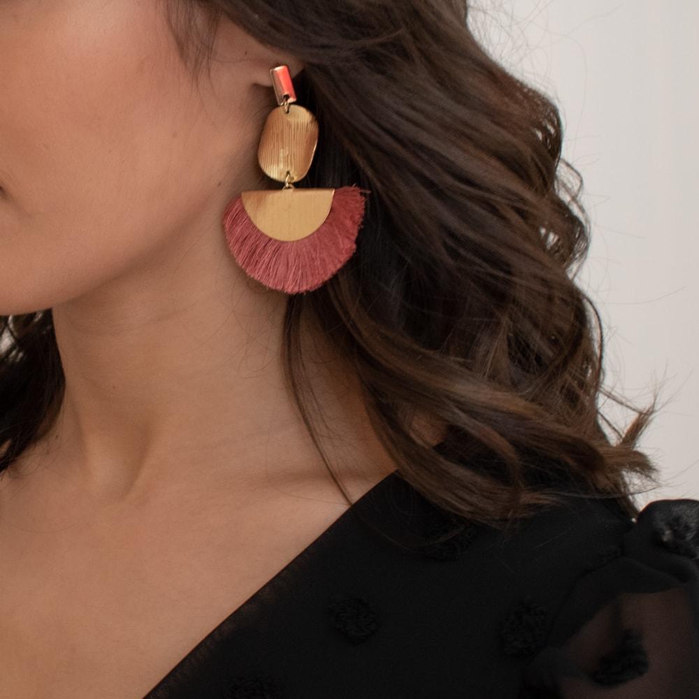 boucle d'oreille franges roses et dorées portées par une femme