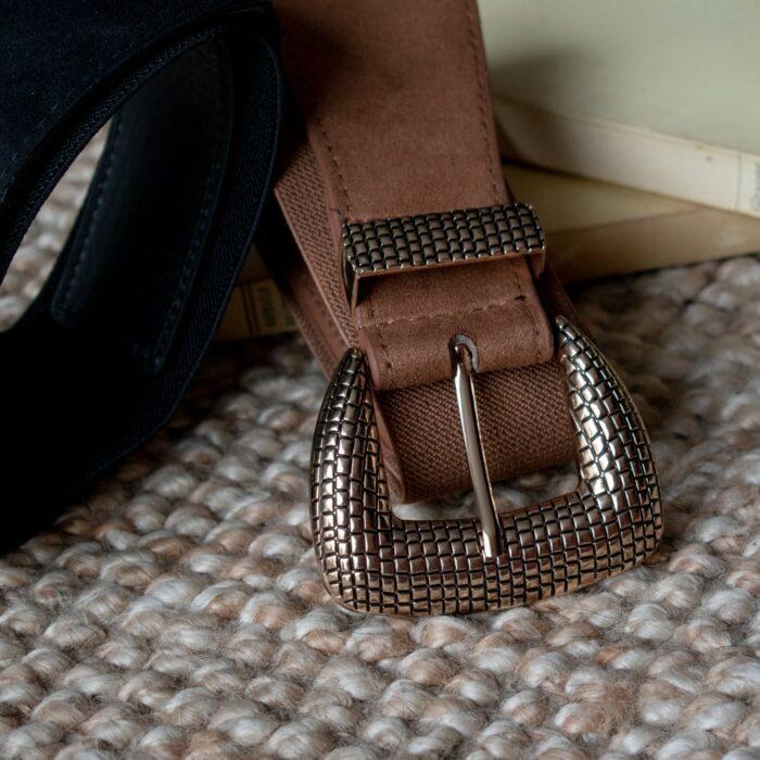 zoom sur une ceinture en cuir et elastique avec grosse boucle dorée