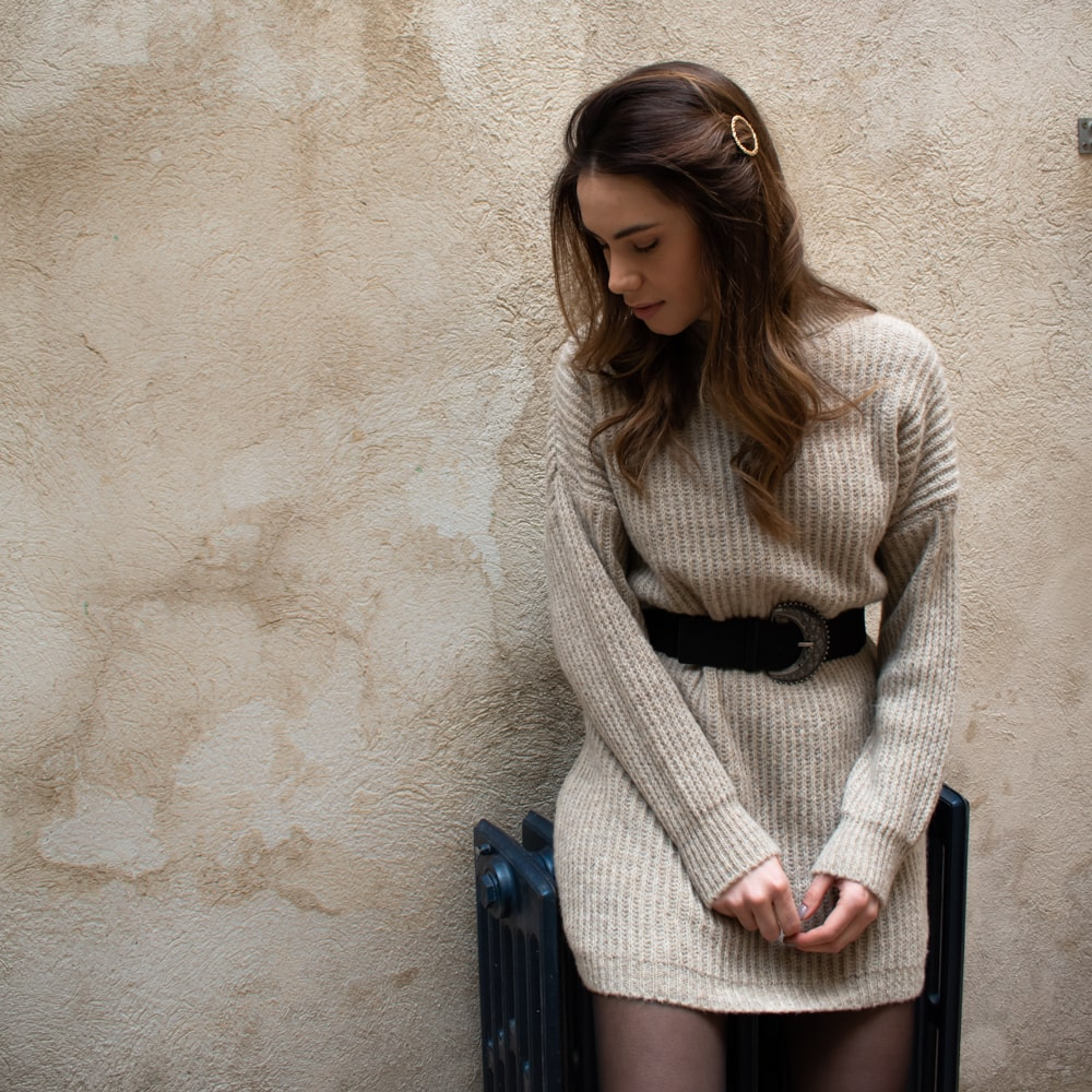 femme adossée à un mur portant une robe pull beige