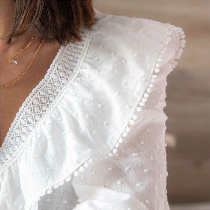 zoom sur un volant d'une femme portant une blouse blanche à plumetis