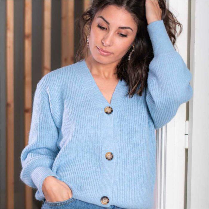 femme portant un gilet oversize grosses mailles bleu avec gros boutons