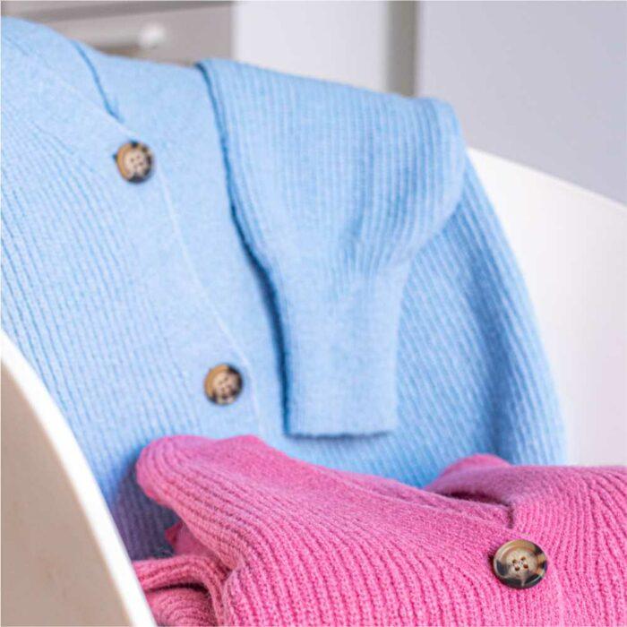 un gilet rose et un gilet bleu posés sur un chaise