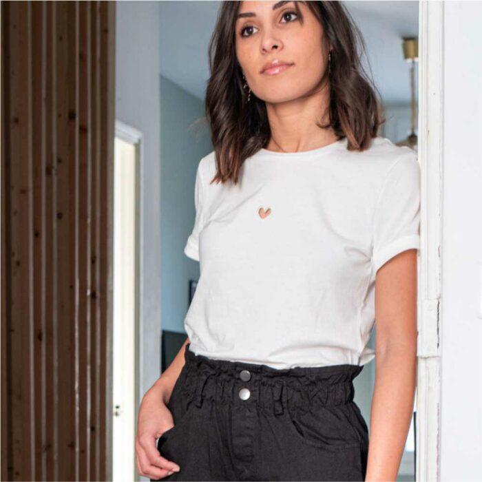 femme portant un t shirt blanc avec petit coeur découpé sur le devant