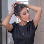 femme portant un t shirt noir et coeur découpé se tenant les cheveux