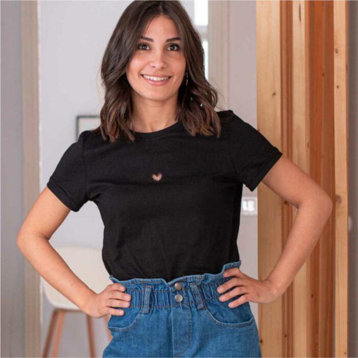 femme mettant ses mains sur les hanches portant un t shirt noir avec coeur vide découpé