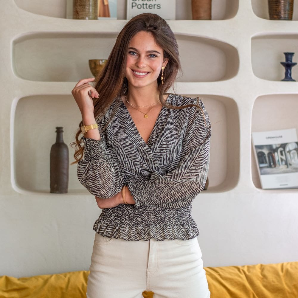 femme portant une blouse beige et noire imprimé rayé