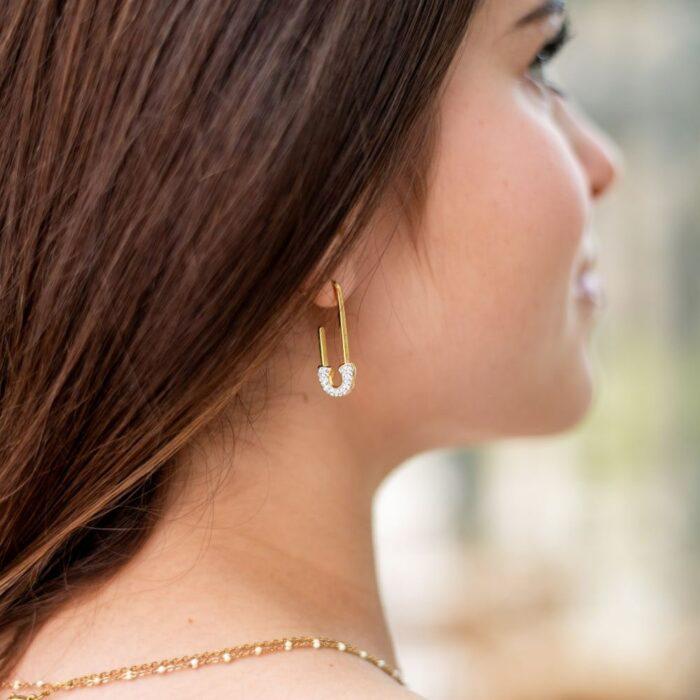 femme portant une boucle d'oreille dorée en forme d'épingle