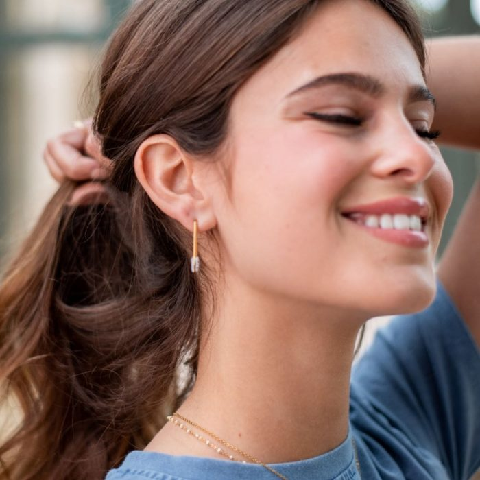 femme portant une boucle d'oreille type épingle à nourrice dorées à strass
