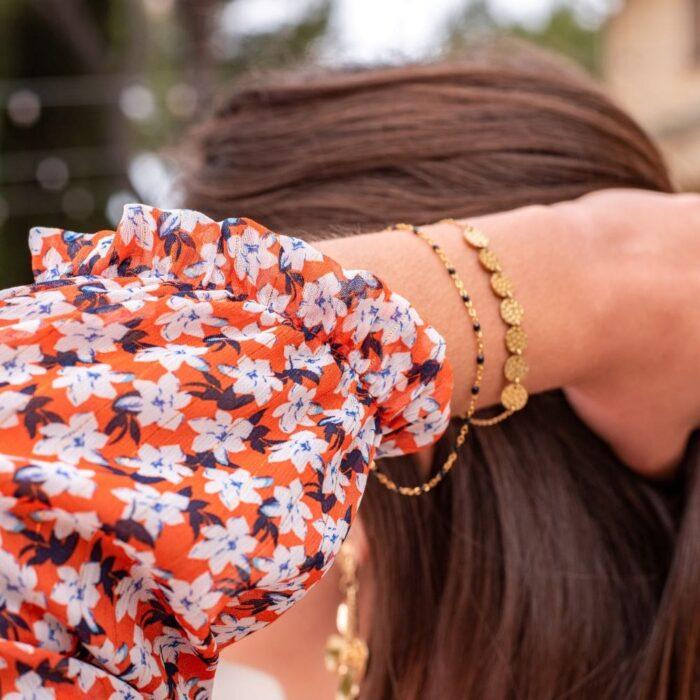 femme portant un bracelet fin doré à pampilles dorées