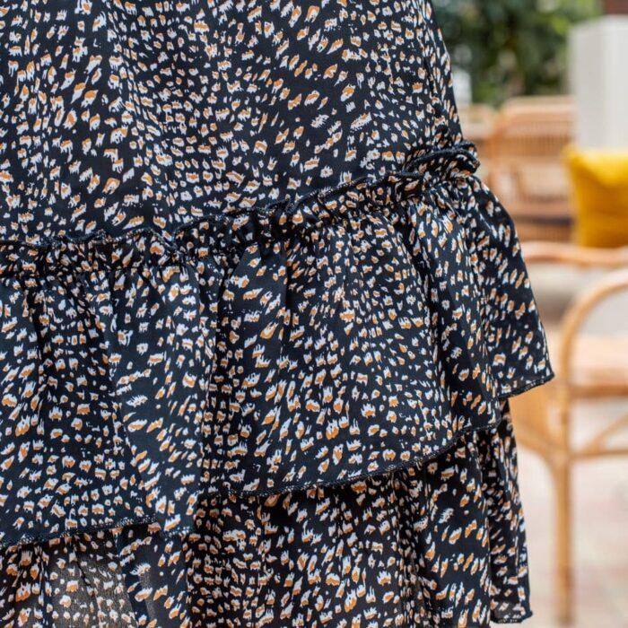 zoom sur l'imprimé léopart d'une jupe noire à volants