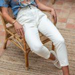 femme assise portant un pantalon blanc taille haute