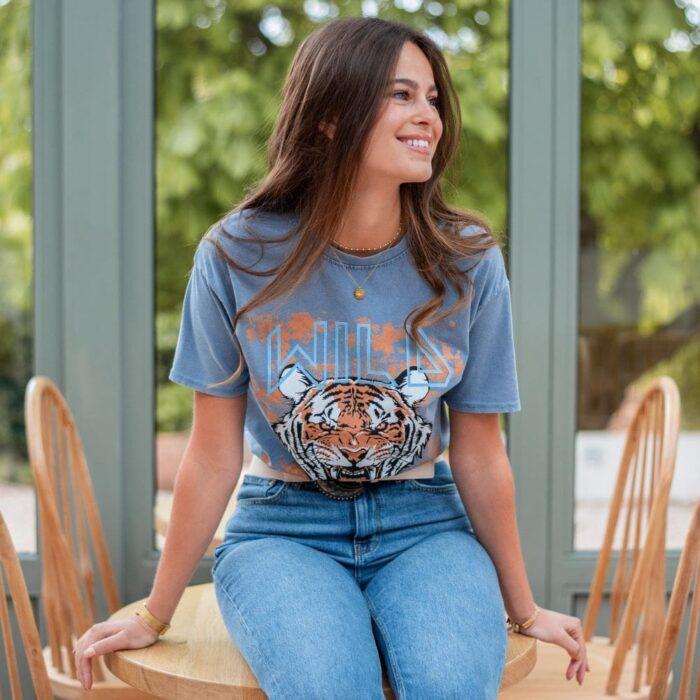 femme assise portant un t shirt imprimé tête de tigre