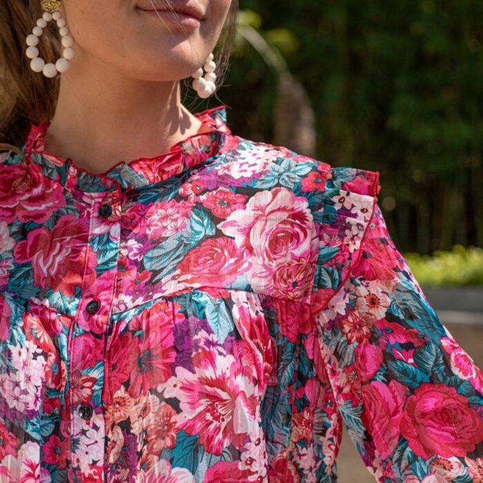 femme portant une blouse à grosses fleurs roses