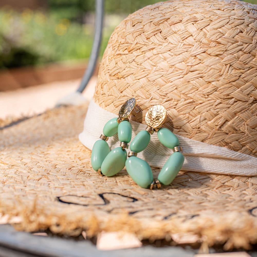 zoom sur boucles d'oreilles grosses fantaisies perles vert sauge sur un chapeau
