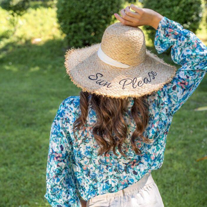 femme portant une blouse fleurie bleu azur se tenant le chapeau de paille