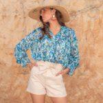 femme portant un look tendance d'été, short paper bag avec chemise bleue et chapeau