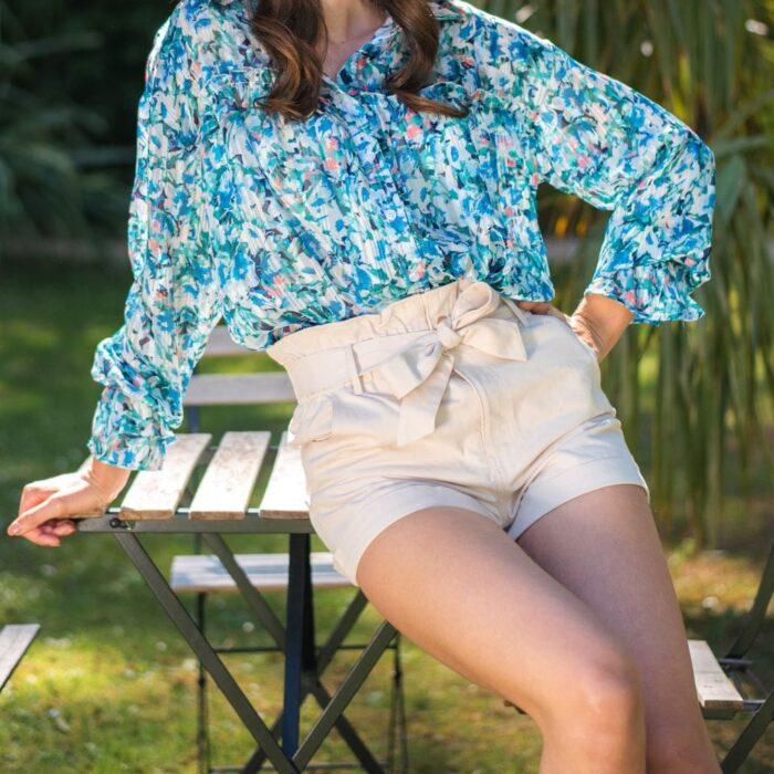 femme assise portant un short paper bag beige et chemise bleue