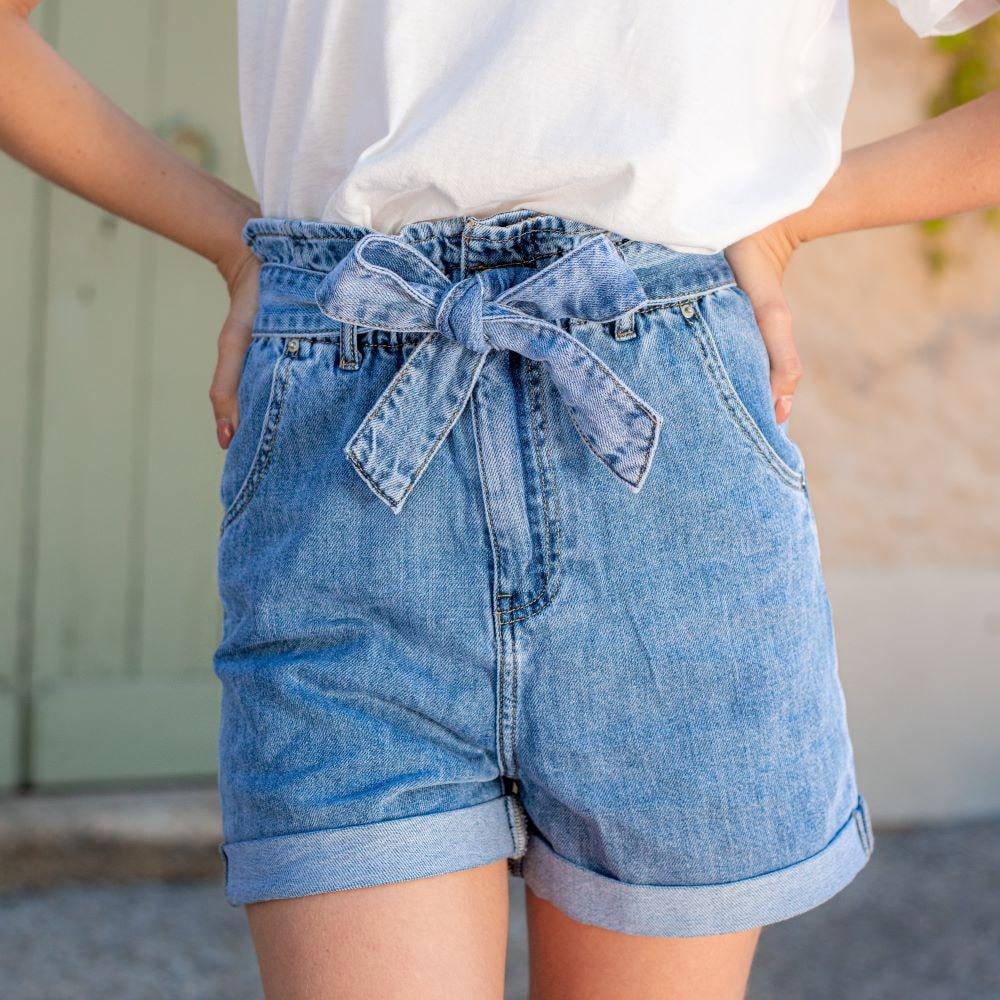femme portant un short bleu en jeans taille haute paper bag