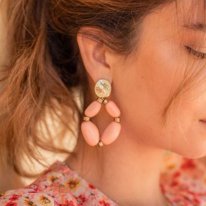 femme portant une grosse paire de boucles d'oreilles fantaisie corail